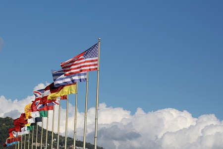 plan éloigné: Photo long shot of row of different national flags flutter in wind on tall flagstaffs green mountains fluffy white clouds on blue sky background, horizontal picture