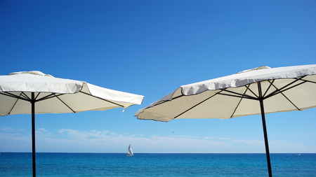bright sky: Photo closeup of two white beach umbrellas for sun protection in line at seashore silhouetted against bright blue sky and sea on seascape background, horizontal picture