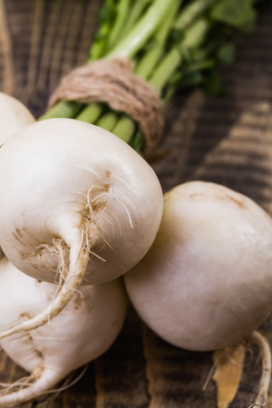 dikon: Closeup photo of bunch of fresh pure white round turnips with greens connected with twine on brown wooden table, vertical picture