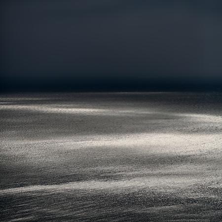 desolaci�n: Foto de la espectacular costa marina y el mar con ondas ondas de baja contra el cielo gris oscuro por la intemperie atardecer sobre el fondo marino, imagen cuadrada