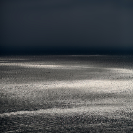desolaci�n: Photo of spectacular marine seashore and sea with ripples low waves against dark grey sky at dusk bleakness over seascape background, square picture