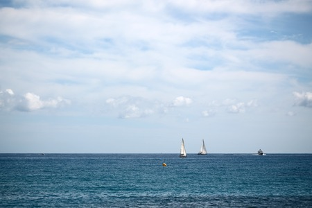 blue vessels: Photo of sea vessels offshore in calm blue sea silhouetted against milky cloudy sky day time on seascape background, horizontal picture Stock Photo