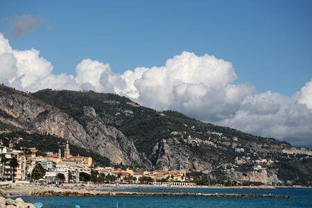 plan éloigné: Photo long shot de la belle vue panoramique de la pittoresque station balnéaire située sur le côté de la mer ci-dessous coteaux montagnes nuages ??blancs sur lumineux fond de ciel bleu, image horizontale
