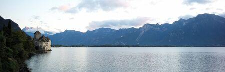 plan éloigné: Photo long shot de la pittoresque paysage estival de la journée paisible au bord de l'eau rive du lac château médiéval arbres verts haute montagne nuages ??blancs sur lumineux fond de ciel bleu, image horizontale