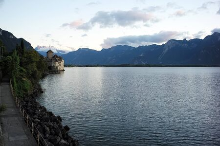 lake shore: Photo closeup of picturesque summer landscape of lake shore waterside promenade medieval castle green trees high mountains white fluffy clouds on milky sky background, horizontal picture