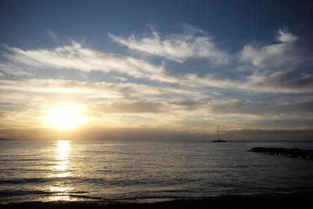 plan �loign�: Photo long shot de la belle marine soir�e calme avec jet�e silhouette sombre de yacht flottant dans la mer contre le coucher du soleil incroyable et bas nuages ??blancs sur horizon marin fond, image horizontale