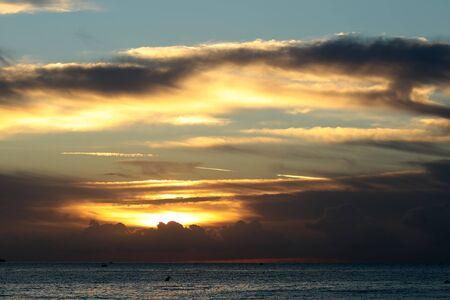 desolaci�n: Foto de la espectacular costa del mar mar azul marino con las ondulaciones contra la iluminaci�n de color amarillo-luz del cielo nublado bajo nivel en intemperie atardecer puesta del sol sobre el fondo marino, cuadro horizontal