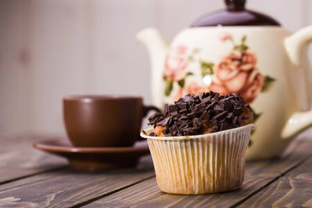 paper basket: Appetizing tasty fresh muffin in paper basket with chocolate crust on top standing near brown cup of coffee and beautiful teapot on wooden table on light blur background closeup studio, horizontal Stock Photo