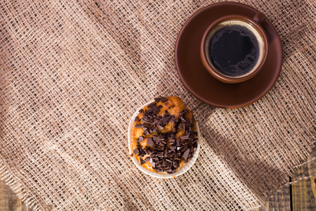chocolate pieces: Brown beautiful cup of hot fresh black coffee on saucer and appetizing sweet cupcake with chocolate pieces tasty breakfast on sackcloth indoor top view, horizontal picture