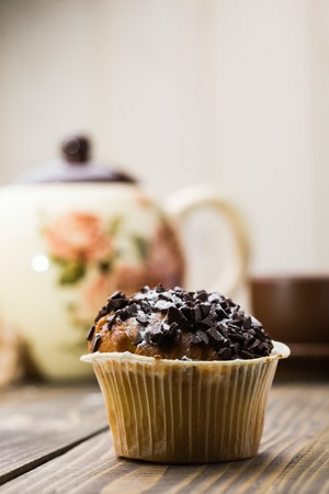 paper basket: Fresh tasty dessert chocolate muffin in paper basket on wooden table in background of cute teapot unhealthy food with many calories culinary copyspace indoor closeup on light background, vertical Stock Photo