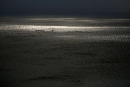 desolación: Foto del barco remolcador en la espectacular costa marítima y el mar con ondas ondas de baja contra el cielo gris oscuro por la intemperie atardecer sobre el fondo marino, cuadro horizontal