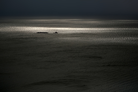 desolaci�n: Photo of tug boat on spectacular maritime seashore and sea with ripples low waves against dark grey sky at dusk bleakness over seascape background, horizontal picture