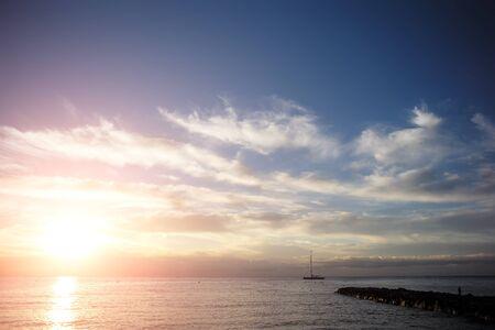 plan éloigné: Photo long shot de la belle marine soirée calme avec jetée silhouette sombre de yacht flottant dans la mer contre le coucher du soleil rose incroyable et bas nuages ??blancs sur horizon marin fond, image horizontale