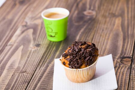 paper basket: Appetizing tasty sweet muffin in paper basket decorated by chocolate crust standing on white napkin in background of bright green glass of coffee on wooden table closeup studio, horizontal picture
