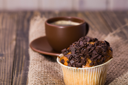 fattening: Sweet delicious cupcake decorated by chocolate chips near brown beautiful cup of aromatic coffee standing on sackcloth tasty lunch fattening meal studio closeup on wooden background, horizontal