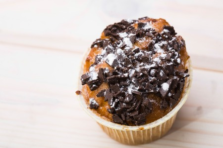 fattening: One fresh delicious muffin decorated by chocolate and powdered sugar fattening meal unhealthy food pastries carbohydrates studio on light background top view closeup copyspace, horizontal picture Stock Photo