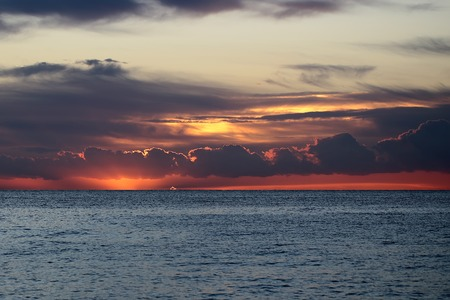 desolaci�n: Photo of spectacular marine seashore blue sea with ripples against flame coloured low level cloudy sky at sunset time dusk bleakness over seascape background, horizontal picture