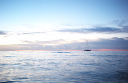sailingboat: Photo of sailing-boat yacht offshore in calm blue sea silhouetted against milky cloudy sky after sunset on seascape background, horizontal picture Stock Photo