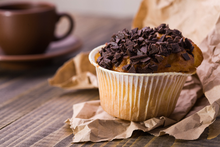 american dessert: American traditional appetizing holiday dessert sweet warm cupcake with chocolate pieces on top in paper basket standing on brown wrapper on wooden table closeup studio, horizontal picture