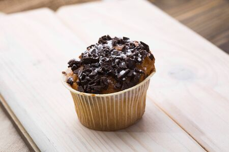 fattening: One baked fragrant fresh appetizing cupcake in paper case with chocolate fattening meal carbohydrates meal with many calories refreshment on light wooden board studio closeup, horizontal picture Stock Photo
