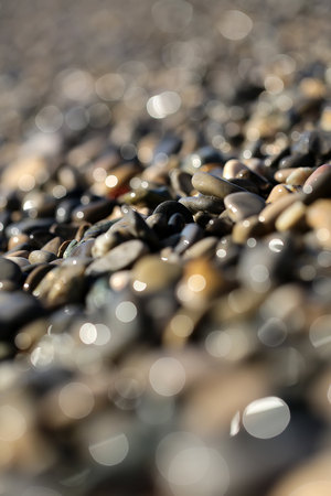 shingle beach: Photo blurred closeup large quantities of wet grey smooth fragments clasts of marine rubbles pebbles stones rocks of various sizes forms surface outdoor on shingle beach background, vertical picture Stock Photo