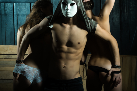naked youth: Three sensual young adult people of handsome muscular man with hidden face by mask with attractive naked girls with slim body  in erotic panties in sexual relations indoor on wood backdrop, horizontal