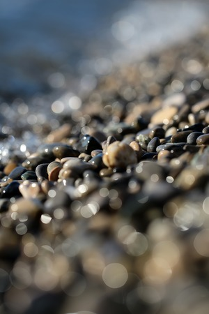 quantities: Photo blurred closeup large quantities of wet grey smooth fragments clasts of marine rubbles pebbles stones rocks of various sizes forms surface outdoor on shingle beach background, vertical picture Stock Photo