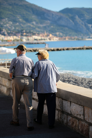 welldressed: Photo back view of well-dressed silver-haired senior couple aged man and woman promenade walking arm-in-arm along beach blue sea bright sky mountains on seascape background, vertical picture