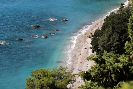 shingle beach: Photo of beautiful seaside seen from above shingle beach line blue sea and rich green foliage trees water-based leisure area on coastlines background, horizontal picture Stock Photo