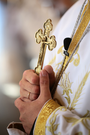 sacramental: Beautiful golden cross in male hands of priest wearing white robe on wedding ceremony in christian cathedral church holy sacramental event marriage closeup, vertical picture