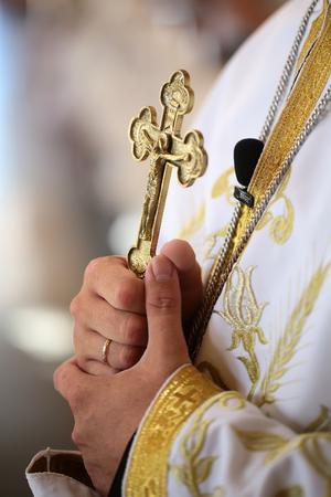 familia cristiana: cruz de oro hermosa en manos de los hombres de sacerdote llevaba túnica blanca en la ceremonia de la boda en la iglesia catedral cristiana santa evento sacramental del matrimonio primer plano, imagen vertical