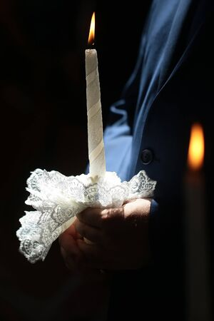 sacramental: Burning canddle decorated by white beautiful lace in male hand of groom wearing in dark blue suit in church on wedding ceremony sacramental happy moment closeup indoor, vertical picture