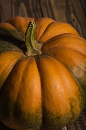 Closeup photo of top part of whole big ripe round orange pumpkin with smooth segmented surface and green spots on brown wooden table, vertical picture