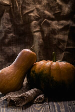 flattened: Rustic still life of two whole raw orange long gourd and round flattened with green formless blotch squash decorated with burlap on wooden table, vertical photo Stock Photo