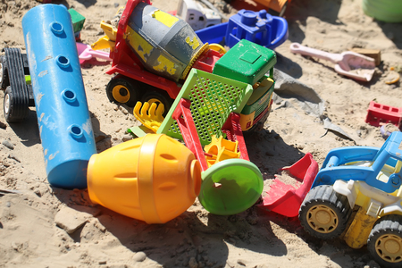 playtime: Many beautiful childish plastic multicolored toys car lorry small rake on sand background in summer playtime boyish activity closeup, vertical picture Stock Photo