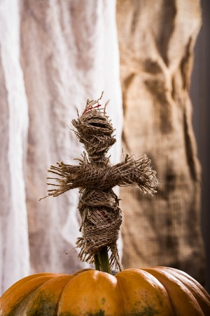 cross linked: Closeup photo of handmade cross shaped Halloween sackcloth witching doll put on stem of round orange segmented cucurbita on white and brown fabric background, vertical picture