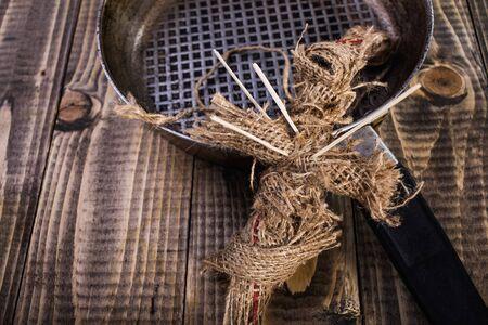 pierced: Closeup photo of handcraft cross shaped Halloween burlap voodoo doll pierced with sticks on chest near round pan with clew of cord on wooden table, horizontal picture Stock Photo