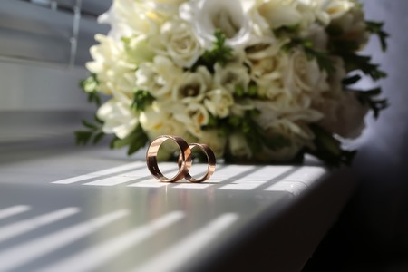 splendid: Two beautiful wedding golden rings tradition jewelry symbol of love and unity on wedding ceremony in background of splendid bridal bunch of creamy white roses and tulips closeup indoor, horizontal Stock Photo