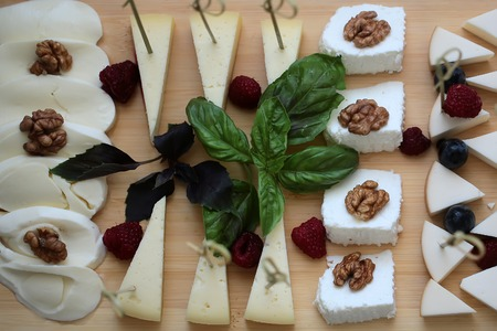 cheese platter: Tasty delicious beautiful cheese platter many pieces food dairy delicatessen product decorated by walnut green balis leaf strawberry grapes on wooden background closeup top view, horizontal picture Stock Photo