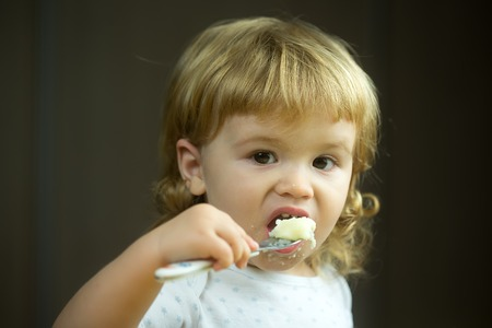 gente comiendo: retrato de vista de detalle de un niño pequeño bebé adorable con el pelo rubio comer alimentos saludables de avena o sémola coocked con la cuchara en la mano foto de interior, horizontal