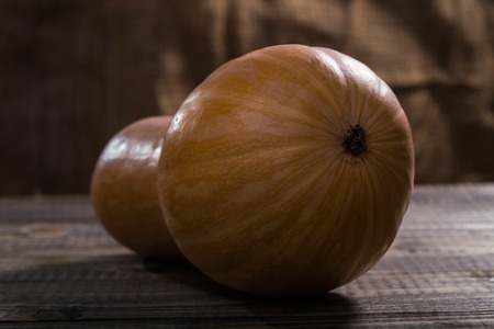 front end: Front end of raw orange with yellow blotch long pear shaped pumpkin with smooth peel lies on brown wooden table on burlap background, horizontal photo Stock Photo