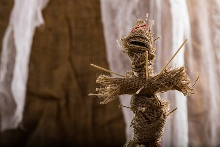 pierced: Closeup photo of spooky ritual burlap voodoo doll pierced with sticks on chest on white and brown canvas background, horizontal picture