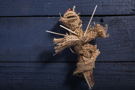 pierced: One cross shaped Halloween rag voodoo doll pierced with sticks on chest on blue wooden timber background, horizontal photo