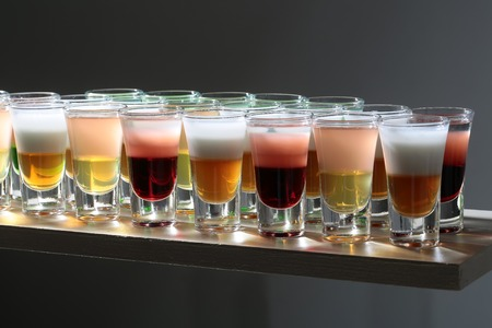 shooter drink: Set of beautiful multicolored red yellow golden and white sweet shots cocktail alcohol drink in glasses standing on bar on grey background, horizontal picture Stock Photo