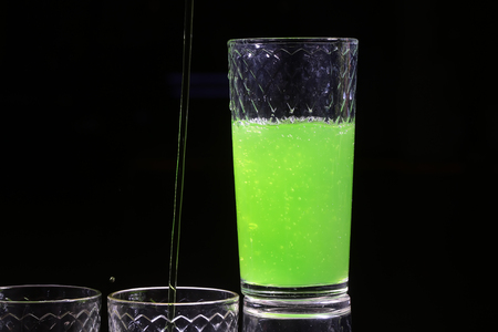 shooter drink: One beautiful bright green colored tasty sweet alcoholic cocktail shooter shot in white glass for night party made of tequila drink fresh lime juice and mint on black background closeup, horizontal