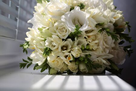 marrying: Closeup of wonderful elegant tender bridal bouquet of creamy tulips and roses flowers for marrying ceremony day natural beauty floral decor on white shadow background, horizontal picture