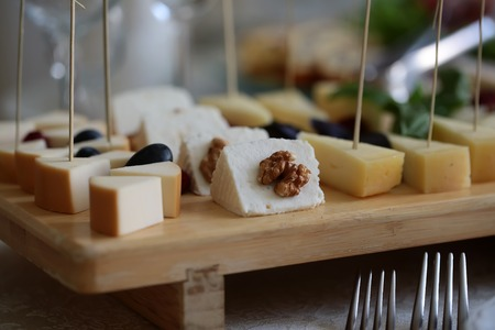 different types of cheese: Appetizing tasty beautiful pieces of cheese decorated by fresh walnuts and grapes laying on wooden board plate dairy cuisine food with protein and fat closeup on blur background side view, horizontal