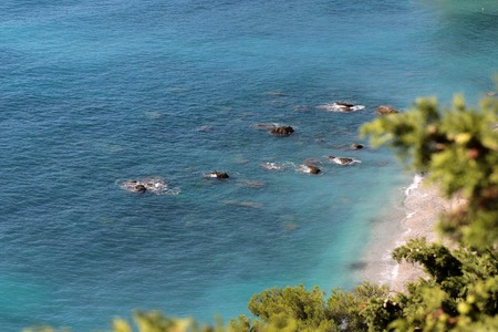 shingle beach: Photo of beautiful seaside seen from above shingle beach line blue sea and blurred green foliage trees water-based leisure area on coastlines background, horizontal picture