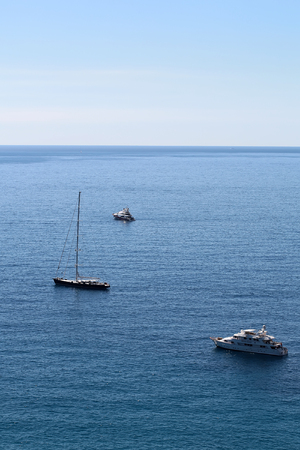 blue vessels: Photo of modern and classic yachts sailing boats vessels offshore in calm blue sea silhouetted against clear sky day time on beautiful seascape background, vertical picture