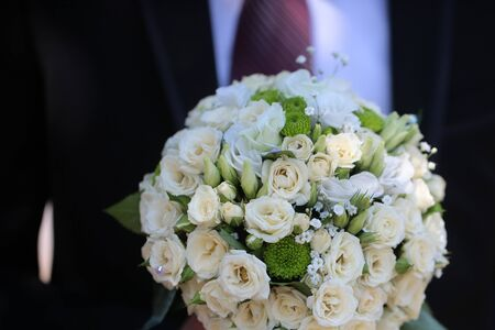 matrimony: Pretty cute bridal wedding decor bouquet of fresh creamy white roses and green flowers marriage nuptials on background of groom tie and suit matrimony decoration closeup, horizontal picture Stock Photo